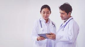 Γιατροί που ελέγχουν τις πληροφορίες ασθενών για μια συσκευή ταμπλετών στοκ φωτογραφία με δικαίωμα ελεύθερης χρήσης