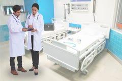 Γιατροί που ελέγχουν τις πληροφορίες ασθενών για μια συσκευή ταμπλετών στοκ εικόνες με δικαίωμα ελεύθερης χρήσης