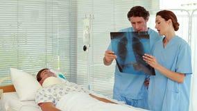 Γιατροί που εξετάζουν την υπομονετική ακτίνα X φιλμ μικρού μήκους