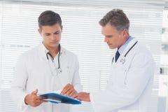 Γιατροί που διαβάζουν έναν φάκελλο Στοκ φωτογραφία με δικαίωμα ελεύθερης χρήσης