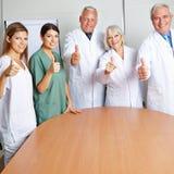 Γιατροί που κρατούν τους αντίχειρές τους επάνω Στοκ φωτογραφία με δικαίωμα ελεύθερης χρήσης