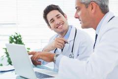 Γιατροί που μιλούν μαζί για κάτι στο lap-top τους στοκ φωτογραφία
