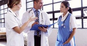 Γιατροί που μιλούν μαζί ενώ γράφοντας σημειώσεις για την περιοχή αποκομμάτων απόθεμα βίντεο