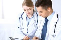 Γιατροί που συζητούν τη μορφή αρχείων φαρμάκων ή που μελετούν στην ιατρική διάσκεψη Έννοια υγειονομικής περίθαλψης, ασφάλειας και στοκ εικόνα