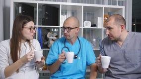 Γιατροί στον καφέ κατανάλωσης σαλονιών του γιατρού και ομιλία στο σπάσιμο φιλμ μικρού μήκους