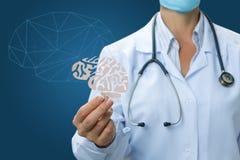 Γιατρός ένα χέρι που κρατά έναν εγκέφαλο από το έγγραφο Στοκ εικόνες με δικαίωμα ελεύθερης χρήσης