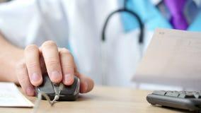 Γιατρός ιατρικής που απασχολείται και που χρησιμοποιεί στο ποντίκι στον υπολογιστή απόθεμα βίντεο