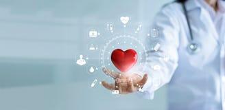 Γιατρός ιατρικής που κρατά την κόκκινη μορφή καρδιών με το ιατρικό δίκτυο εικονιδίων
