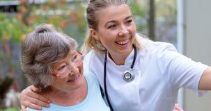 Γιατρός και ανώτερη γυναίκα που παίρνουν selfie στο homeyard 4k απόθεμα βίντεο