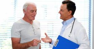 Γιατρός και ανώτερο άτομο που χαμογελούν ενώ διοργανώνοντας τη συζήτηση πέρα από μια έκθεση απόθεμα βίντεο