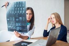 Γιατρός και ασθενής γυναικών που εξετάζουν την ακτίνα X ή Στοκ Εικόνες