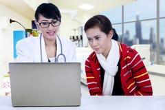 Γιατρός και ασθενής που εξετάζουν το lap-top Στοκ Φωτογραφία