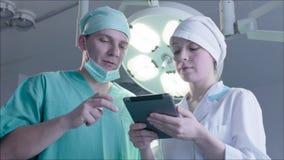 Γιατρός και η νοσοκόμα που χρησιμοποιούν μια ταμπλέτα στο λειτουργούν δωμάτιο απόθεμα βίντεο