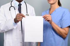 Γιατρός και νοσοκόμα που κρατούν ψηλά ένα κενό άσπρο σημάδι Στοκ Φωτογραφίες
