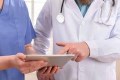 Γιατρός και νοσοκόμα που συζητούν τις δοκιμές ασθενών στον υπολογιστή ταμπλετών στο νοσοκομείο στοκ φωτογραφία με δικαίωμα ελεύθερης χρήσης
