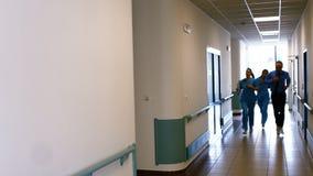 Γιατρός και νοσοκόμα που τρέχουν στο πέρασμα του νοσοκομείου φιλμ μικρού μήκους