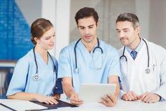 Γιατρός και συνάδελφοι που χρησιμοποιούν την ψηφιακή ταμπλέτα στεμένος στο γραφείο Στοκ φωτογραφία με δικαίωμα ελεύθερης χρήσης
