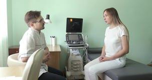 Γιατρός και υπομονετική συνεδρίαση και ομιλία στο διαγνωστικό δωμάτιο υπερήχου φιλμ μικρού μήκους