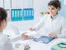 Γιατρός και υπομονετική συνεδρίαση στο γραφείο στοκ εικόνες