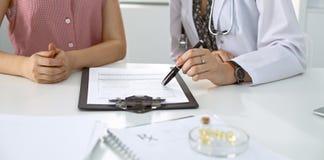 Γιατρός και υπομονετική συνεδρίαση στο γραφείο Παθολόγος που δείχνει στα αρχεία ιατρικού ιστορικού και που εξηγεί κάτι Στοκ Φωτογραφίες