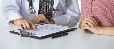 Γιατρός και υπομονετική συνεδρίαση στο γραφείο Παθολόγος που δείχνει στα αρχεία ιατρικού ιστορικού και που εξηγεί κάτι Στοκ Εικόνες