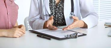 Γιατρός και υπομονετική συνεδρίαση στο γραφείο Παθολόγος που δείχνει στα αρχεία ιατρικού ιστορικού και που εξηγεί κάτι Στοκ φωτογραφία με δικαίωμα ελεύθερης χρήσης