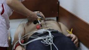 Γιατρός καρδιολόγων που προετοιμάζει τον ασθενή για την αφαίρεση του καρδιογραφήματος απόθεμα βίντεο