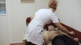 Γιατρός καρδιολόγων που προετοιμάζει τον ασθενή για την αφαίρεση του καρδιογραφήματος φιλμ μικρού μήκους