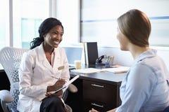 Γιατρός κατόπιν διαβουλεύσεων με το θηλυκό ασθενή στην αρχή στοκ εικόνες