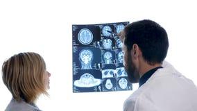 Γιατρός με έναν ασθενή που ελέγχει μια ανίχνευση MRI μπροστά από τη μεγάλη άσπρη επίδειξη φιλμ μικρού μήκους