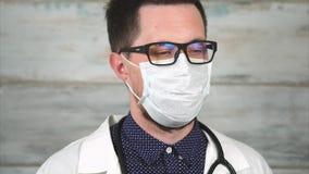 Γιατρός με ένα ακριβές βλέμμα Πορτρέτο ενός ατόμου στα γυαλιά και την ιατρική μάσκα φιλμ μικρού μήκους
