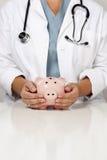Γιατρός με τα χέρια φροντίδας σε μια τράπεζα Piggy Στοκ Φωτογραφίες