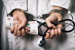 Γιατρός με τα χρήματα στις χειροπέδες Η έννοια της δωροδοκίας στην ιατρική και τη δωροδοκία στοκ φωτογραφίες