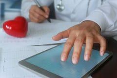 Γιατρός με την κόκκινη μορφή και την ταμπλέτα καρδιών Στοκ φωτογραφία με δικαίωμα ελεύθερης χρήσης