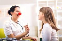 Γιατρός με τη μύτη κλόουν και ευτυχής ασθενής παιδιών Στοκ εικόνες με δικαίωμα ελεύθερης χρήσης