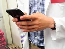 Γιατρός με το άσπρο παλτό Texting στο κινητό τηλέφωνο στοκ φωτογραφία με δικαίωμα ελεύθερης χρήσης