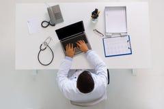 Γιατρός με το καρδιογράφημα και lap-top στην κλινική Στοκ Φωτογραφίες