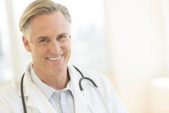 Γιατρός με το στηθοσκόπιο γύρω από το λαιμό που χαμογελά στο νοσοκομείο Στοκ Εικόνες