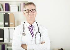 Γιατρός με το στηθοσκόπιο γύρω από το λαιμό του που εξετάζει τη κάμερα Στοκ εικόνα με δικαίωμα ελεύθερης χρήσης