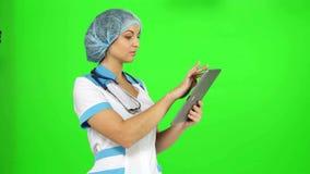 Γιατρός με το στηθοσκόπιο και μια ταμπλέτα στα χέρια απόθεμα βίντεο