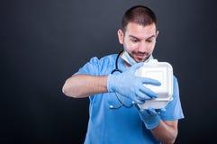 Γιατρός με το στηθοσκόπιο που εξετάζει ευτυχής το καλαθάκι με φαγητό του Στοκ Φωτογραφία