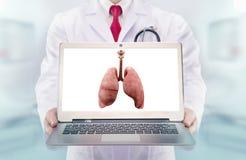 Γιατρός με το στηθοσκόπιο σε ένα νοσοκομείο πνεύμονες στο όργανο ελέγχου lap-top στοκ φωτογραφία
