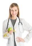 Γιατρός με το χέρι στην εκμετάλλευση Apple ισχίων και το μέτρο ταινιών Στοκ φωτογραφία με δικαίωμα ελεύθερης χρήσης