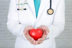 Γιατρός νεαρών άνδρων που κρατά μια κόκκινη καρδιά, που στέκεται στον τοίχο backgroun Στοκ Εικόνα
