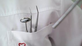 Γιατρός οδοντιάτρων που παίρνει τα οδοντικά εργαλεία απόθεμα βίντεο