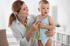Γιατρός παιδιών που εξετάζει το μικρό παιδί με το στηθοσκόπιο στοκ φωτογραφίες με δικαίωμα ελεύθερης χρήσης