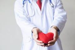 Γιατρός που δίνει ένα αντικείμενο μορφής καρδιών απομονωμένο στο λευκό υπόβαθρο Στοκ εικόνες με δικαίωμα ελεύθερης χρήσης