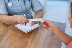 Γιατρός που δίνει μια συνταγή στον ασθενή της στο ιατρικό γραφείο Στοκ Φωτογραφία