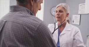 Γιατρός που ακούει το ποσοστό καρδιών του ασθενή με το στηθοσκόπιο στοκ φωτογραφία