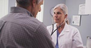 Γιατρός που ακούει το ποσοστό καρδιών του ασθενή με το στηθοσκόπιο στοκ φωτογραφίες με δικαίωμα ελεύθερης χρήσης